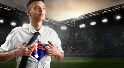 Australia soccer or football supporter showing flag under his business shirt on stadium.