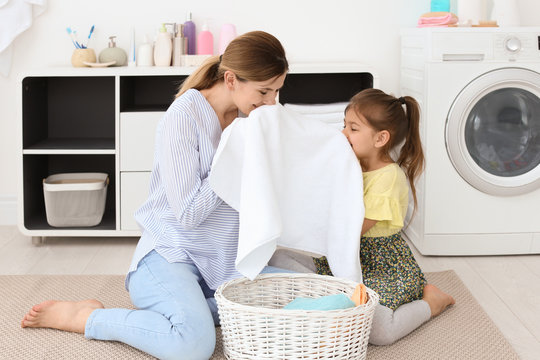 Housewife with daughter folding freshly washed towels in laundry room