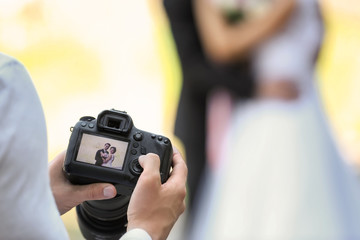 Professional photographer with camera and wedding couple, outdoors