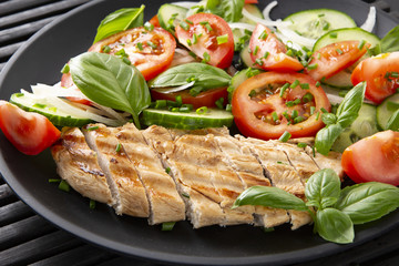 Vegetable salad and grilled chicken on a black background. Healthy food. Diet.