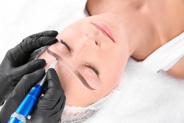 Young woman undergoing eyebrow correction procedure in salon