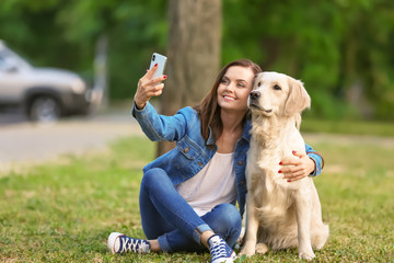 Young woman taking selfie together with her dog in park. Pet care
