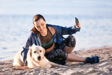 Young woman taking selfie with together her dog on beach. Pet care