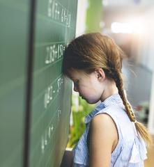 Trauriges Mädchen versucht schwierige Mathematik Aufgaben zu lösen