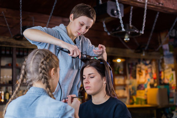 Make-up artist and hairdresser working with woman client