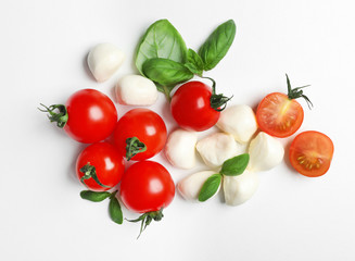 Tuinposter Groenten Ripe red tomatoes, mozzarella cheese balls and basil on white background, top view