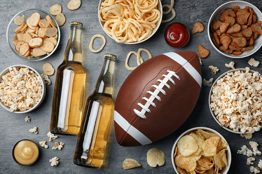 Table full of tasty snacks and beer prepared for watching American football on TV, top view