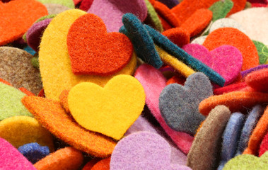 background of many colored hearts made of felt