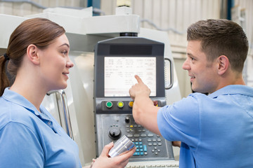 Engineer Instructing Female Apprentice On Use Of CNC Machine