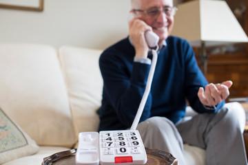 Senior Man Using Telephone With Oversized Keypad At Home