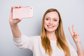 Portrait of trendy peaceful girl with beaming smile shooting selfie on smart phone gesturing v-sign with two fingers isolated on grey background