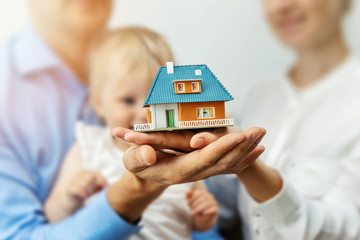 new home concept - young family with dream house scale model in hands