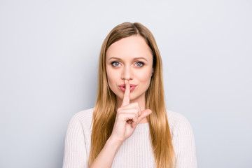 Shh! Portrait of charming trendy seductive tempting girl asking for silence gesturing sign with forefinger looking at camera isolated on grey background