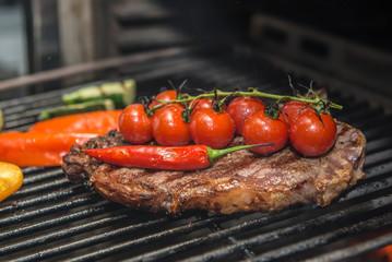 Club Steak and Grilled Vegetables Being Prepared in Josper