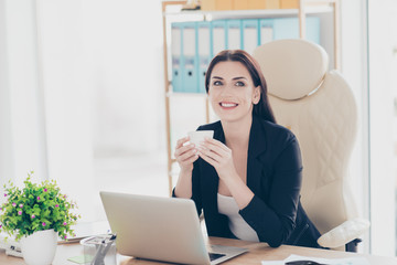 Portrait of joyful glad lawyer holding mug with tea in hands looking away planing journey trip vacation weekend sitting in modern work place