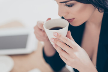 Close up cropped portrait of dreamy lovely woman  drinking coffee holding cup enjoying aroma having pleasure. Recreation idyllic delight concept