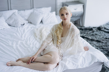 beautiful young woman in negligee on sitting bed
