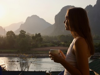 Young woman drinking hot coffee on the balcony with beautiful mountain landscape