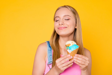 Portrait of cheerful cute lover having vanilla caramel ice cream scoops in hands keeping eyes closed enjoying taste smell aroma isolated on bright vivid yellow background