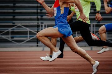 race men sprinters runners in 100 meters at track stadium