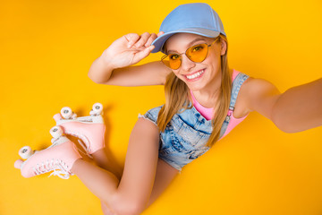 Top view self portrait of positive slim girl with beaming smile shooting selfie on front camera while sitting on ground floor in roller skates isolated on yellow background