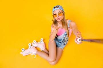 Self portrait of lovely cute girl wearing roller skates jeans overall sitting on floor ground shooting selfie on front camera sending air kiss with hand isolated on yellow background