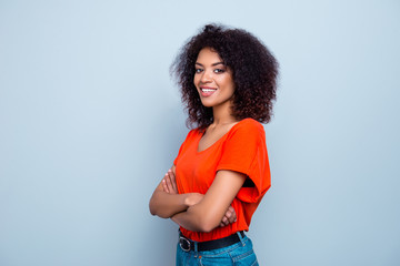 Portrait of joyful cute woman with plump lips modern hairdo in orange t-shirt holding hands crossed looking at camera isolated on grey background