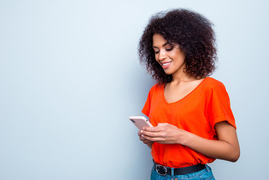 Portrait with copy-space of busy charming woman with modern hairdo in bright outfit holding smart phone in hands using wifi 5G internet checking email searching contact isolated on grey background