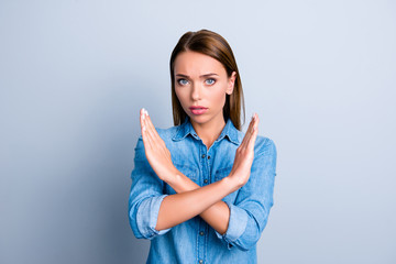 Portrait of sad unhappy woman having her hands cross forbidding something wearing jeans shirt isolated on grey background