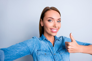 Self portrait of toothy positive girl in casual outfit shooting selfie on front camera showing thumb up sign isolated on grey background