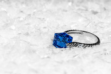 Engagement ring with blue diamond/crystal on white snow background.