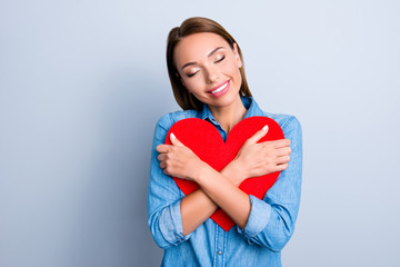 Fall in love! Portrait of lovely sweet girl in jeans shirt embracing big red paper heart figure with close eyes isolated on grey background