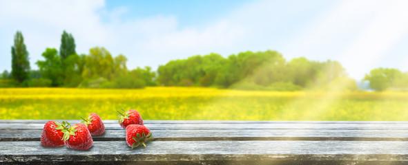 erdbeeren auf holztisch vor landschaft hintergrund