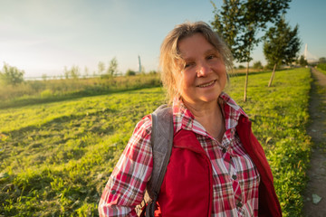 Close up portrait of happy older woman standing outside in summer on field background.
