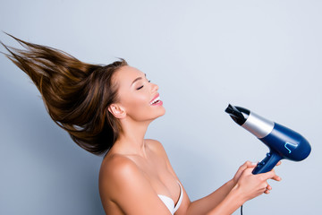 Happiness beautiful therapy natural facial split ends conditioner rest relax laugh mask lotion concept. Profile portrait of excited pretty girl holding hair-dryer isolated on grey background