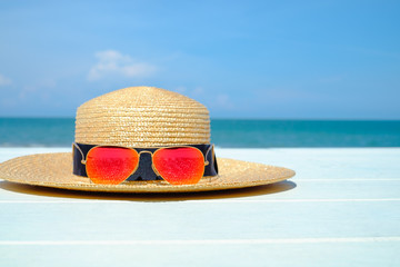 Colorful orange sunglasses on bamboo hat on white wooden table with sea and blue sky cloud background with copy space.summer season.