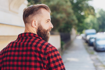 Bearded young man walking down an urban street