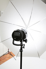 a professional flashlight with a white umbrella for a photo studio