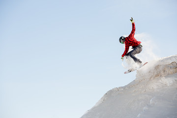 Photo of man in helmet with snowboard jumping from snowy mountain slope