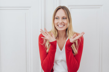 Happy young blond woman clapping her hands