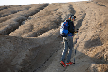 Image from back of growth of female tourist with backpack and sticks for walking on mountain