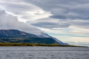 Mountains landscape at sunrise - cloudy sky in pastel colors for your design. Romantic seascape -...
