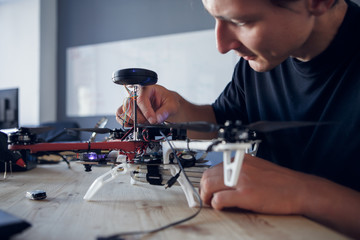 Image of engineer fixing square copter at table