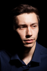 Portrait of young man in his 20s on black background in studio photo