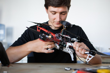 Image of engineer mending square copter at table