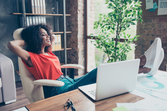 Portrait of pretty cheerful secretary putting legs on table wearing sneakers holding hands behind head looking at window enjoying free time sitting at desk in modern office