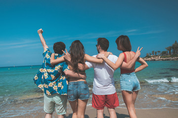 Cheerful young guys and girls are looking at the water with enjoyment. They are standing and embracing while turning back. Funny company entertainment at seaside concept