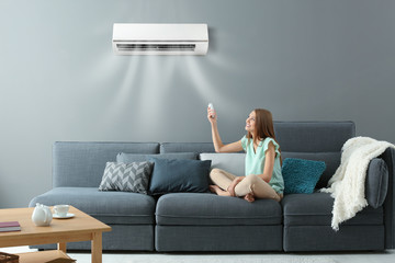 Fototapeta Young woman switching on air conditioner while sitting on sofa at home