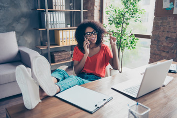 Portrait of funky stylish journalist putting legs on table holding strand of hair speaking by smart phone with lover enjoying freetime sitting in modern comfortable office with interior