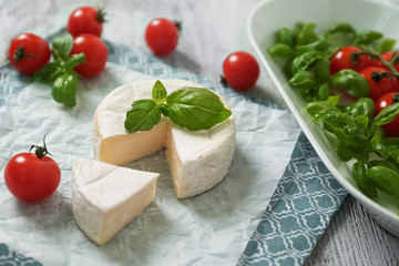 Delicious brie cheese with basil and cherry tomatoes on table